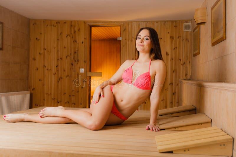 Woman girl relaxing in spa sauna. Wellbeing. Young woman enjoying relaxing in wood finnish spa sauna. Attractive girl in bikini resting. Wellbeing pleasure royalty free stock image