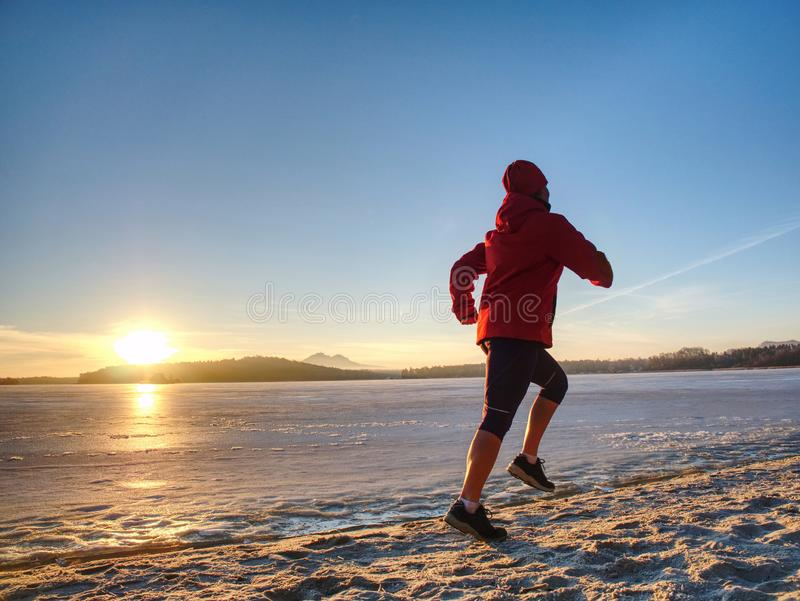 Woman or girl running in winter river park by evening. Happy face royalty free stock images
