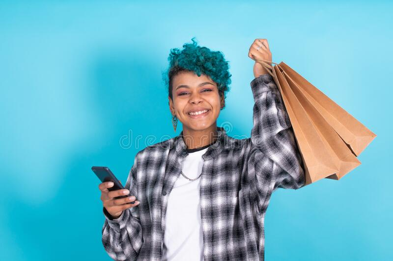 Woman or girl with shopping bags. Isolated woman or girl with shopping bags and mobile phone stock photography
