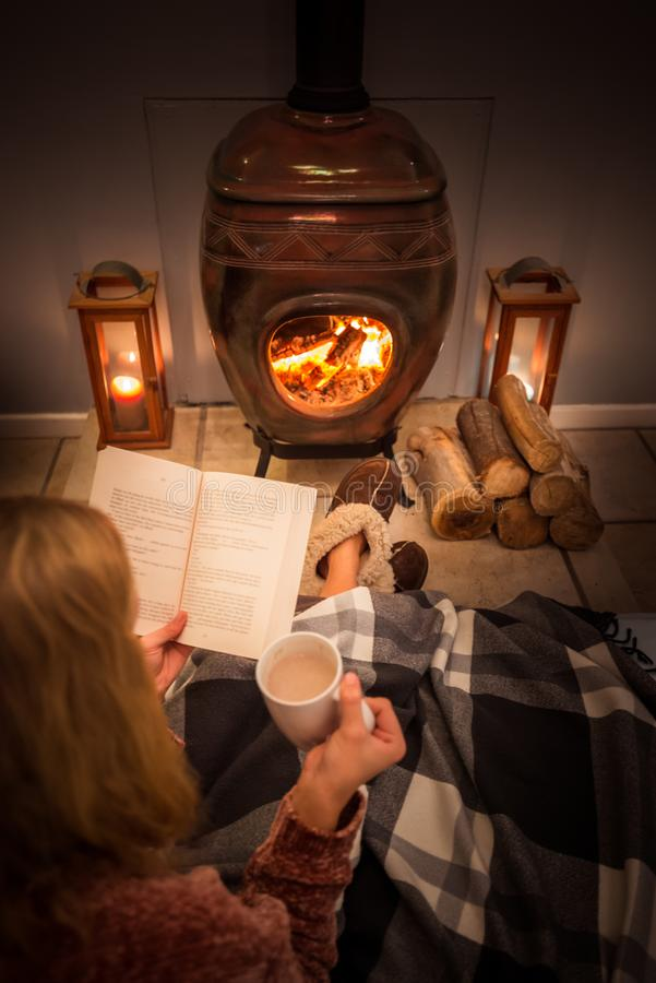 Woman girl sitting in front of a cozy fireplace during winter under a blanket  reading a book drinking coffee/hot chocolate. stock image