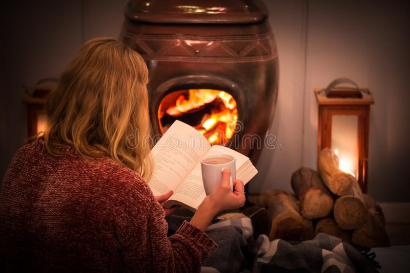 Woman girl sitting in front of a cozy fireplace during winter under a blanket  reading a book drinking coffee/hot chocolate. royalty free stock images