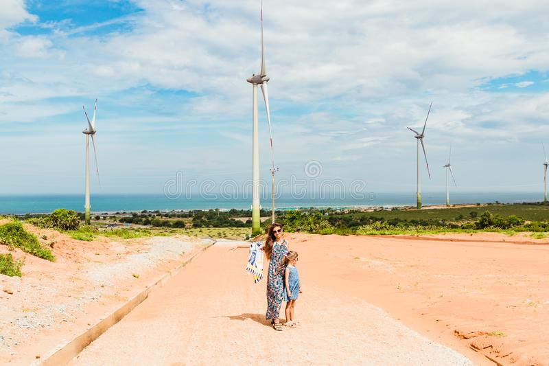 Woman and girl stand near Wind turbine farm from clean energy near the sea. Phan Rang, Vietnam.  royalty free stock photo