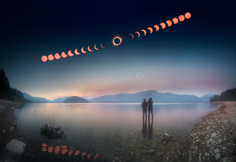 Woman and girl standing in lake watching solar eclipse. This is a stacked photo of a woman and a girl standing in shallow lake and watching the solar eclipse stock image