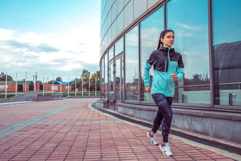 Woman girl in summer jogging in city, sportswear windbreaker leggings. Free space for text. In the morning, a sport stock photos