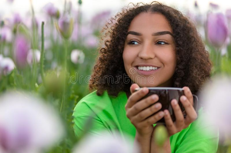 Woman Girl Teenager Field of Flowers Drinking Cup of Coffee or Tea stock photos