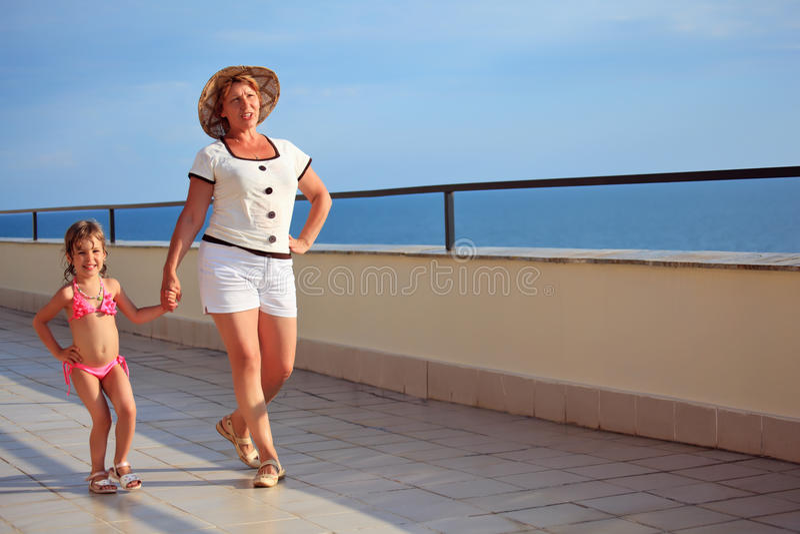 Woman and girl walk on veranda near seacoast royalty free stock images