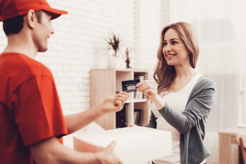 Woman gives bank card deliveryman arab nationality. Courier Delivery. Woman Gives Bank Card. Worker Man Arab Nationality. White Interior. Deliveryman Arab royalty free stock photo