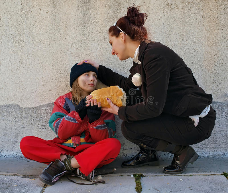 Woman gives bread a beggar child stock image