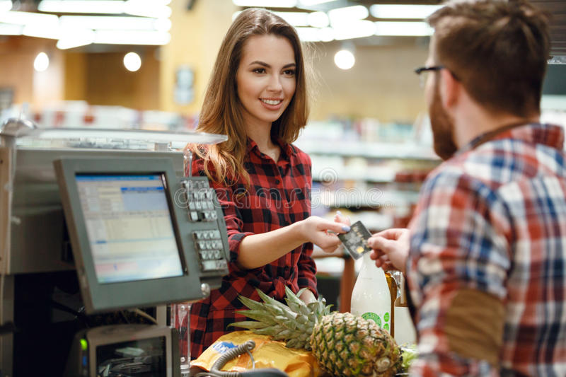 Woman gives credit card to cashier man. Picture of young women gives credit card to cashier men at workspace in supermarket. Looking aside royalty free stock photo