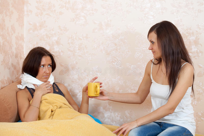 Woman gives cup to unwell girl stock images