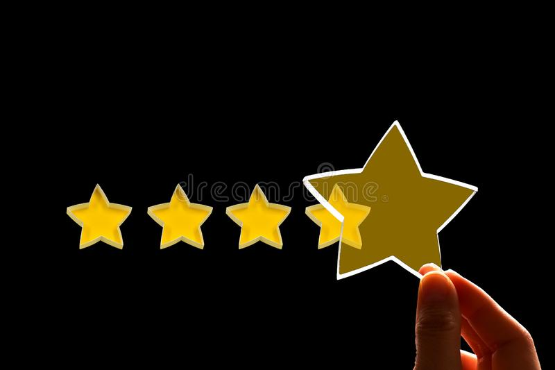 A woman gives a fifth star rating, the concept of a positive rating, reviews and feedback on black. Background stock photo