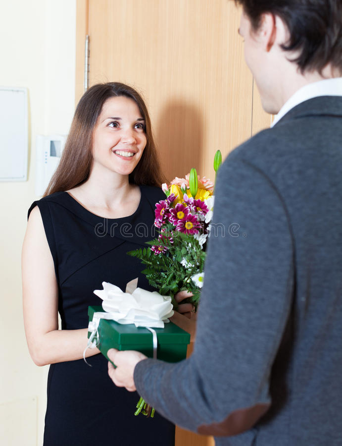 Woman gives a man a gift. Woman gives a men a gift and flowers near the door royalty free stock photography