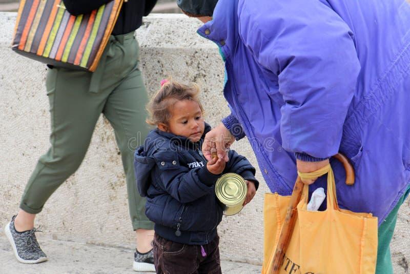 Woman gives money to cute beggar girl downtown of Skopje,capital of Macedonia. SKOPJE, MACEDONIA - OCTOBER 18,2016:Older woman gives money to cute beggar girl stock photo