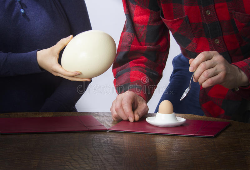 Woman gives ostrich egg to man stock images