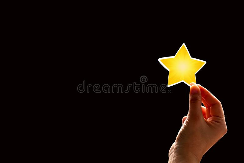 A woman gives a star. The concept of a positive rating, reviews and feedback on black. Background stock image