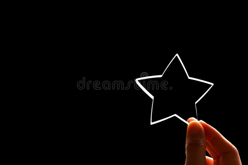 A woman gives a star. The concept of a positive rating, reviews and feedback on black. Background royalty free stock images