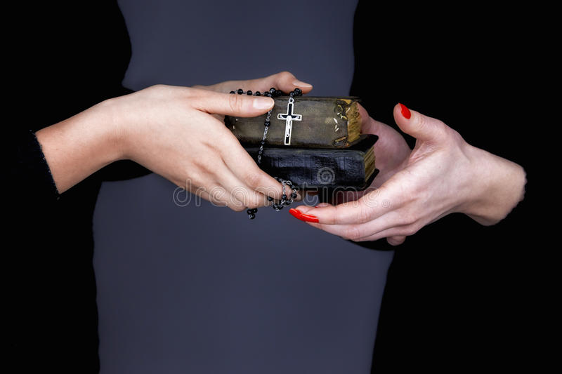 Woman gives two Bibles and rosary to another woman royalty free stock image