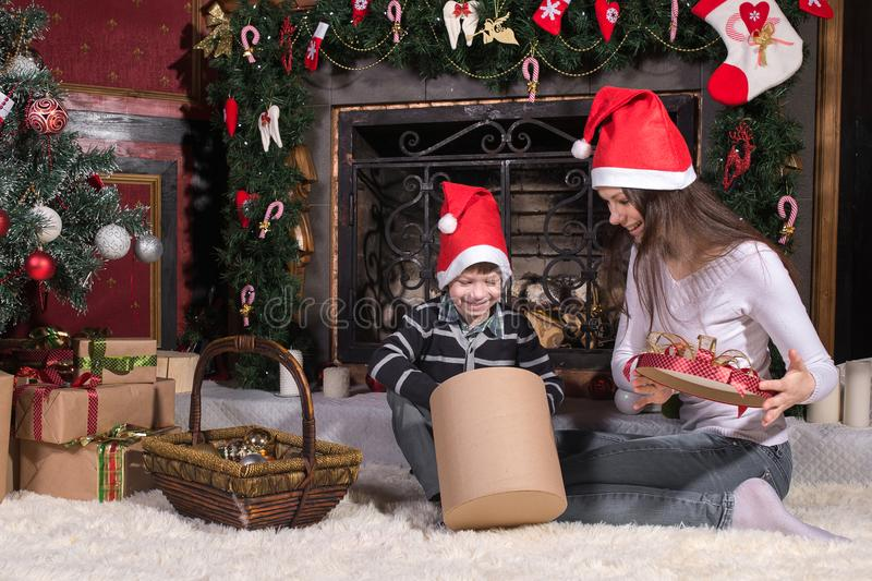 Woman gives wrapped christmas presents gifts to son stock photo
