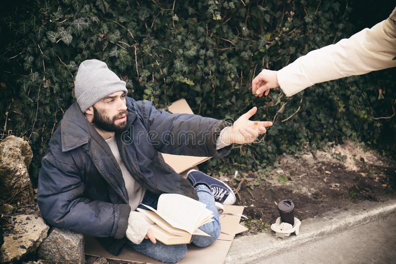 Woman giving alms to poor homeless man on stock images