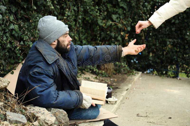 Woman giving alms to poor homeless man stock photo