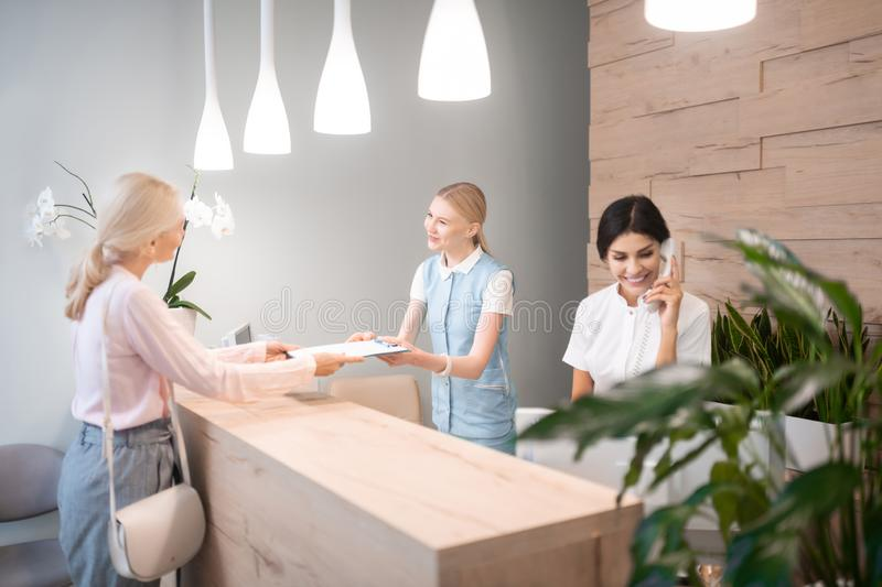 Woman giving back filled up form to administrator. Settling formalities. Happy women standing at reception giving back her filled up form to a polite royalty free stock images