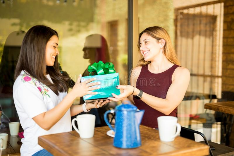 Woman giving a birthday present to friend royalty free stock photography