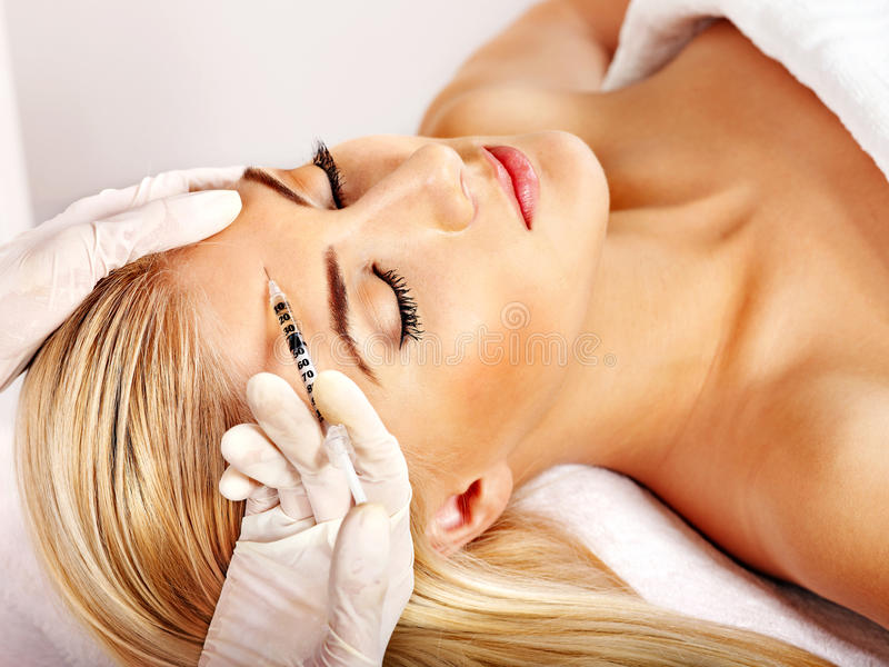 Woman giving botox injections. stock images