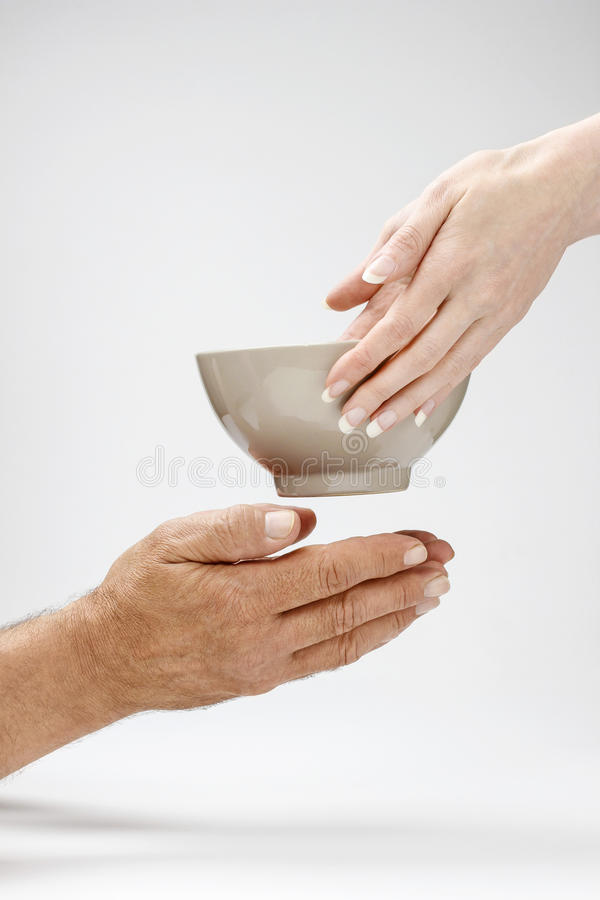 Woman giving bowl of hot meal to the hungry man stock image