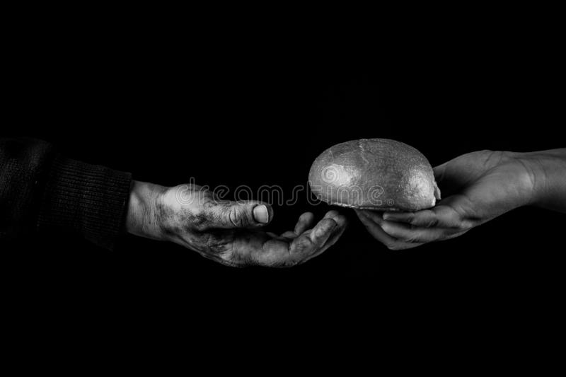 Woman giving Bread to poor man in need. Helping Hand Concept. Black and white stock images