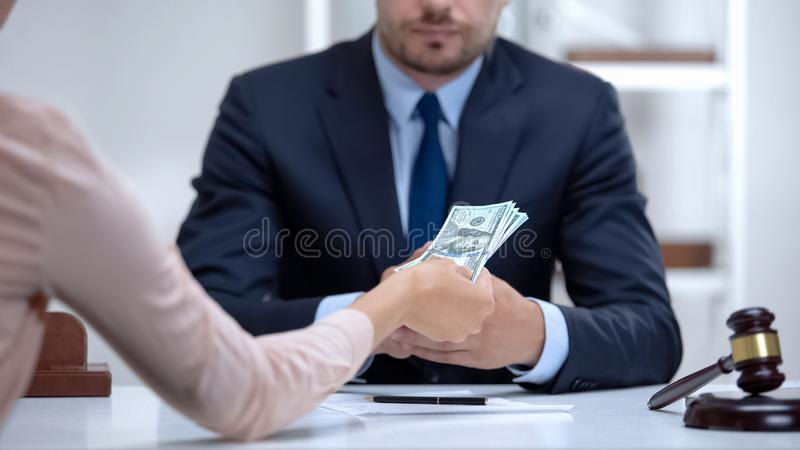 Woman giving bribe to corrupt lawyer, document falsification in illegal business royalty free stock images