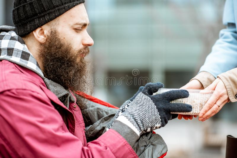 Woman giving food to a homeless beggar. Woman helping homeless beggar giving some food outdoors, close-up view. Concept of helping poor people stock photography