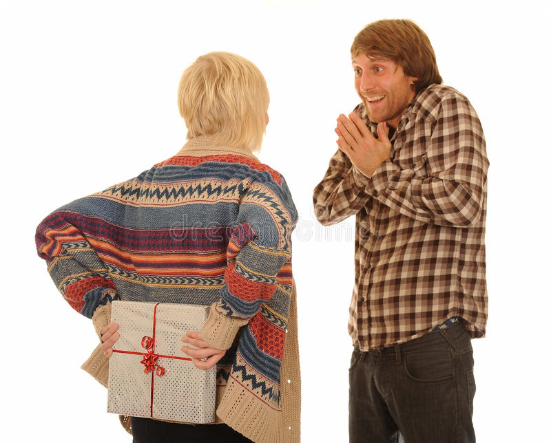 Woman giving man present. Rear view of woman with present behind back looking at happy man, isolated on white background stock image