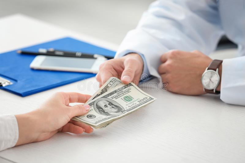 Woman giving money to doctor in office, stock photo