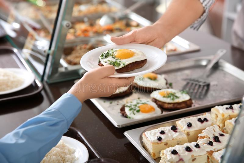 Woman giving plate with healthy food to boy in school canteen royalty free stock image