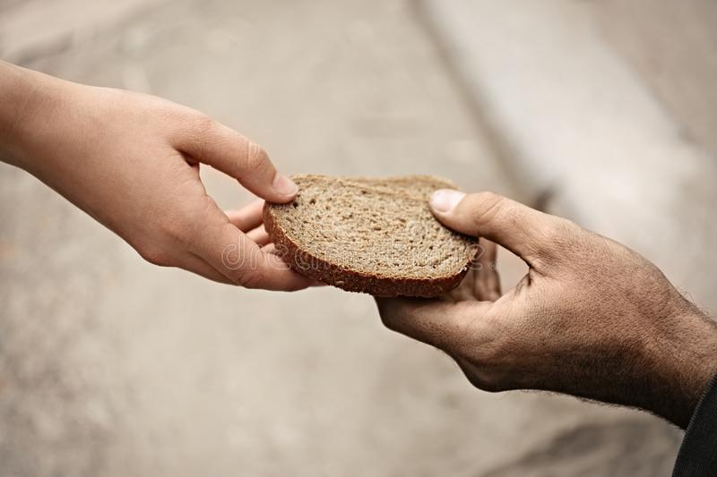 Woman giving poor homeless person pieces of bread outdoors. Closeup stock photo