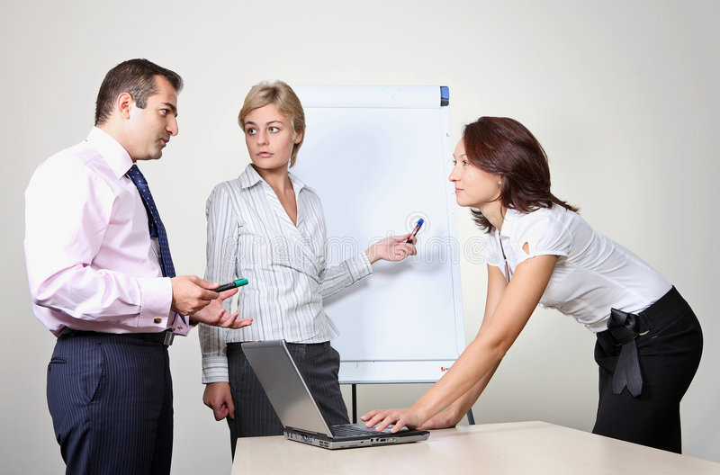 Woman giving a presentation on a flip chart. Three office workers, a woman giving a presentation on a flip chart trying to convince the others stock image