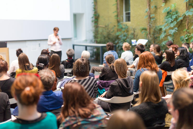 Woman giving presentation in lecture hall at university. royalty free stock photography