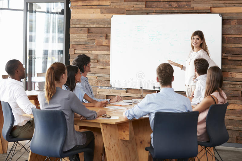 Woman giving a presentation at whiteboard to business team stock images