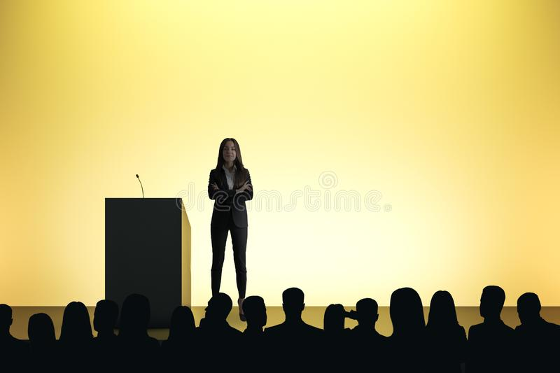 Woman giving speech. In front of backlit audience on light yellow background. Speaker and motivation concept royalty free stock images
