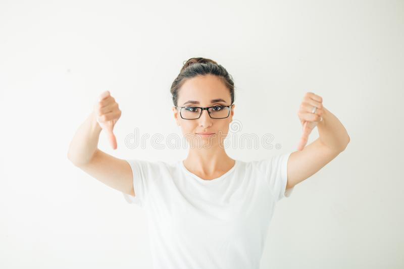 Woman giving thumb down gesture looking with negative expression and disapproval.  stock photo