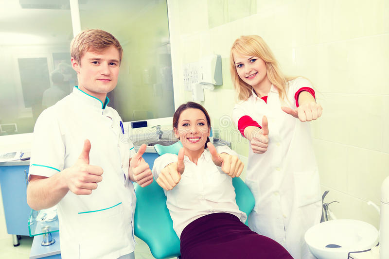 Woman giving thumbs up at dentist office. stock photography