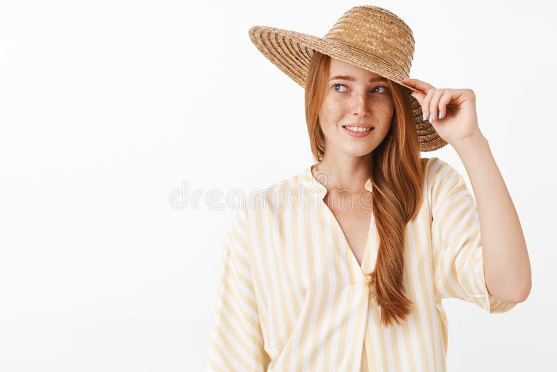 Woman glad she bought awesome straw hat to cover from sun. Portrait of charming and feminine redhead female in striped royalty free stock photography