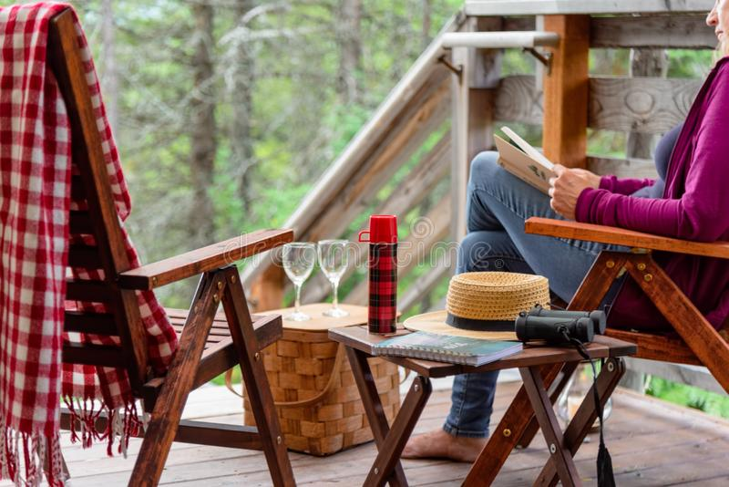 Woman sitting on porch in forest cabin stock photo