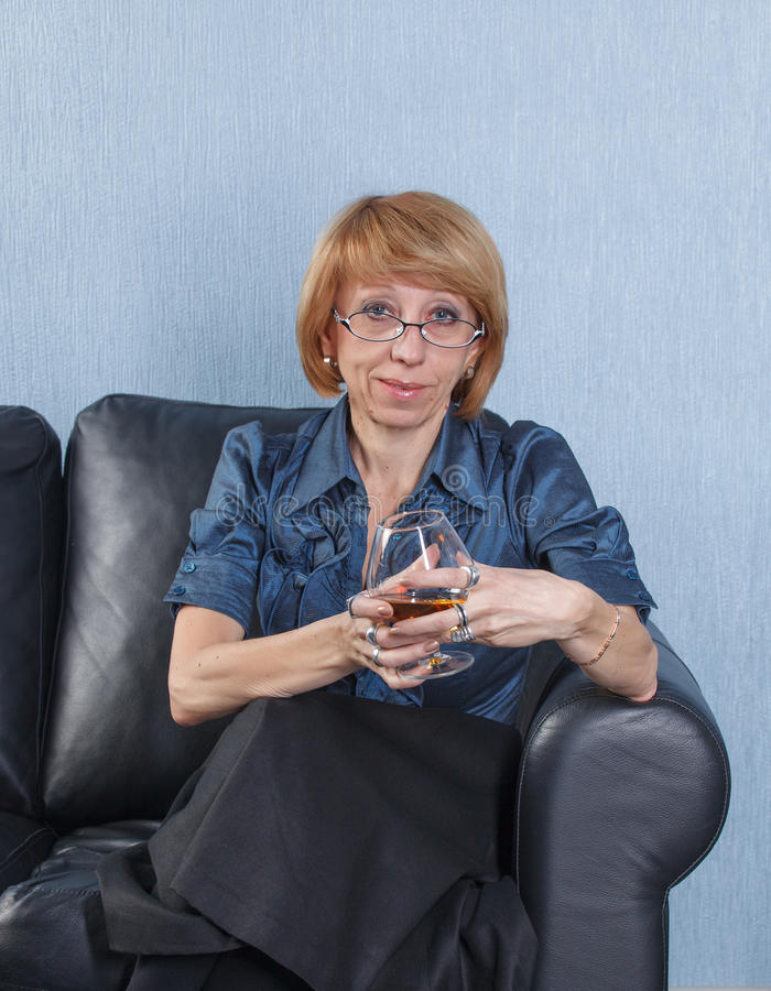 Download Woman With A Glass Brandy On Couch Stock Image - Image: 23860661