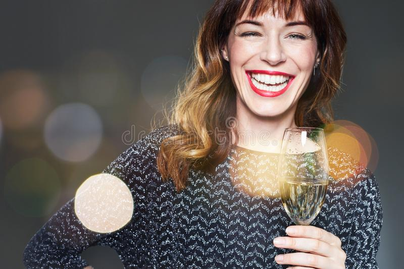 Woman with a glass of champagne on dark background,flares and bokeh. Lady with long curly hair and ref lips celebrating and laughi. Ng stock photo
