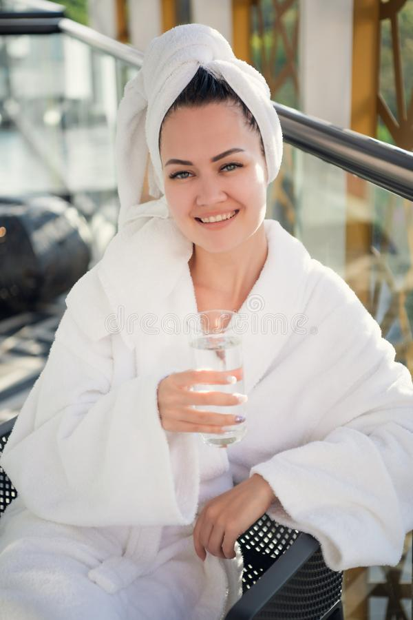 Woman with glass. Cheerful young lady in a bathrobe attending spa center and smiling while sitting on the chair with a royalty free stock image