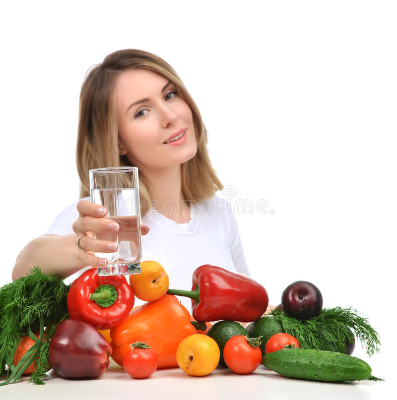 Woman with glass of drinking water and green vegetables and fruits stock images
