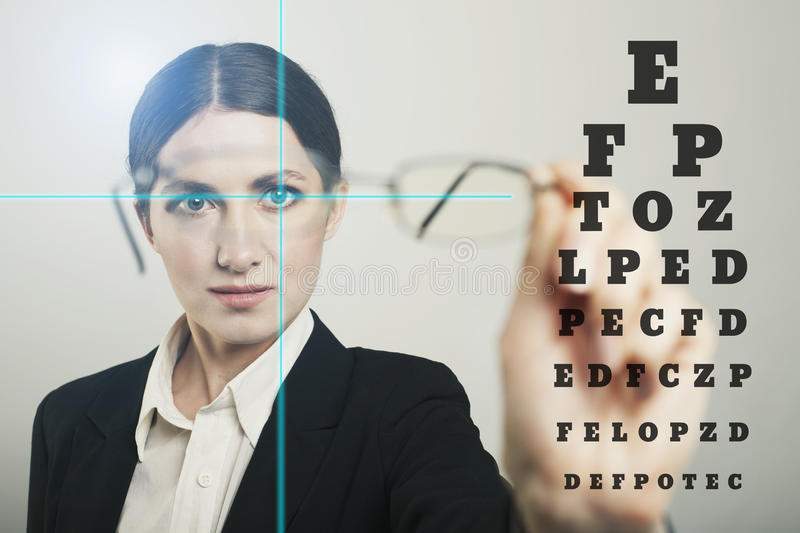 Woman glass with laser hologram and test vision table over dark royalty free stock photography