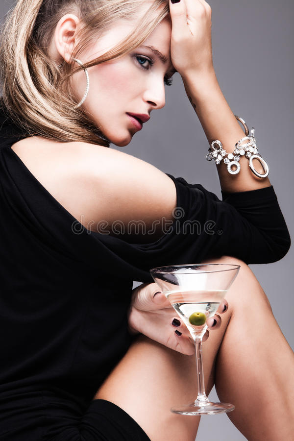 Woman with glass of martini. Young fashion woman with glass of martini, profile, studio shot stock images