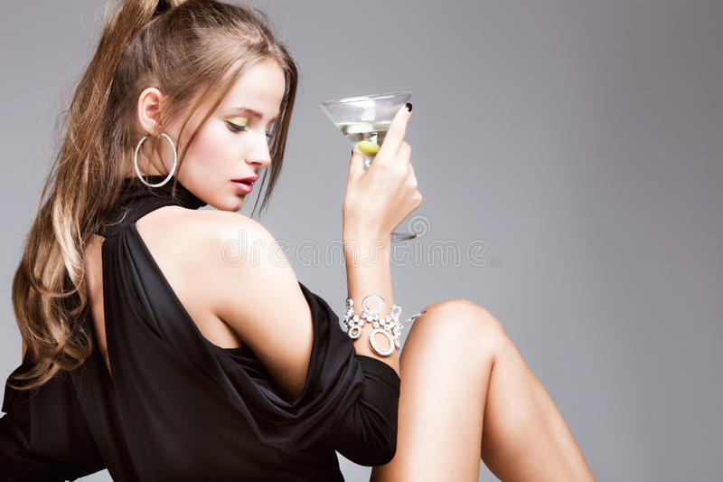 Woman with glass of martini. Young attractive woman with glass of martini, profile, studio shot stock images